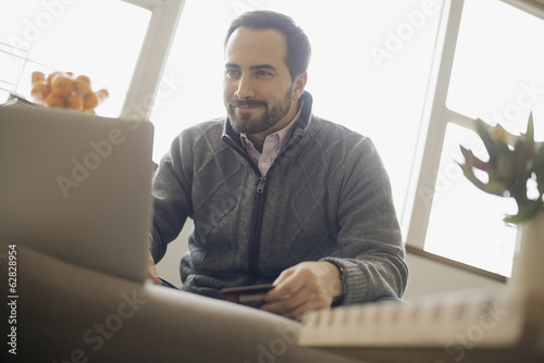 Man on-line shopping on laptop on sofa with credit card
