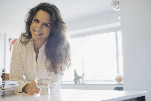Woman at home in kitchen with glass of water