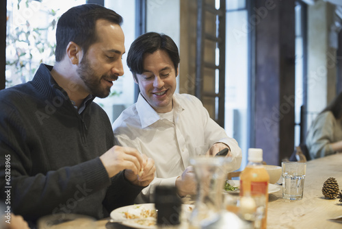 Men sharing text at restaurant table