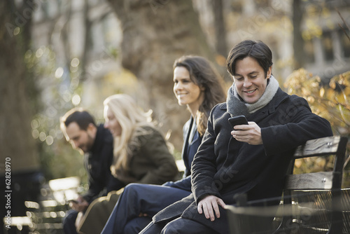 Group on bench in urban park using smartphones