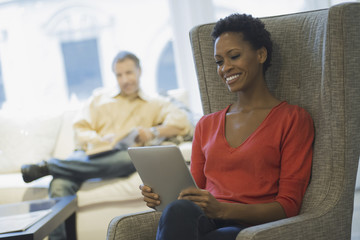 Couple relaxing at home reading, woman with tablet