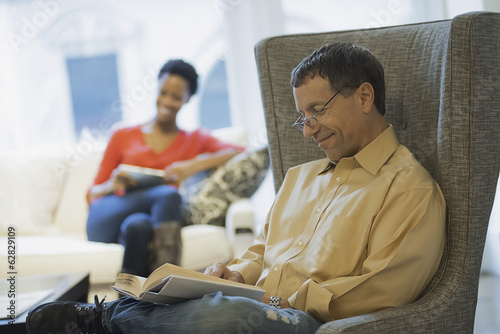 Couple relaxing at home reading