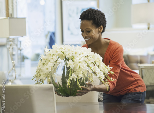 Woman placing vase of flowers on table