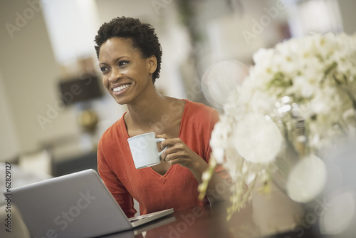 Woman relaxing at home with laptop and coffee