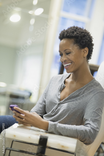 Woman relaxing at home using smartphone