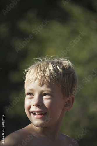 A child turning his head to look over his shoulders, smiling.