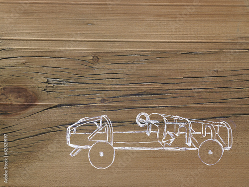 A line drawing image on a natural wood grain background. Side profile of a low sporty open top car chassis.