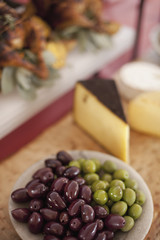 A buffet table laid out for a party. Organic food. A cheese board selection, and a plate of green and black olives.