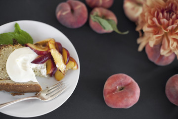 A table viewed from overhead. Organic fruit, peaches, and flowers. a plate with fresh fruit, cake and creme fraiche. A fork. Dessert.