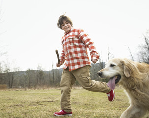 A young boy outdoors on a winter day, holding a stick and running with a golden retriever dog.
