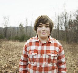 A young boy in a red checked shirt outside on a winter's day.