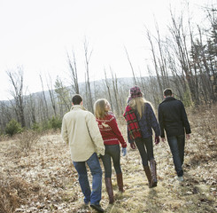 A group of four people walking through woodland on a winter day. Two men and two women.