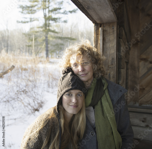 Two people, a mother and daughter, side by side, in the porch of a wooden barn on a farm. A winter's day.