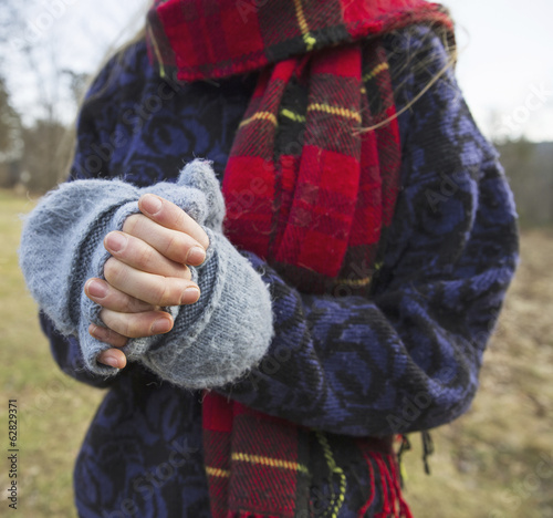 A woman in a tartan scarf and knitted woollen mitts, keeping her hands warm in cold weather.