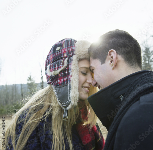 A couple, young man and woman, face to face embracing, outdoors on a cold winter day.