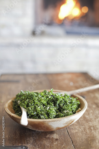 A tabletop with a log fire in the background. Green leafy salad in a wooden bowl.