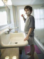 A young boy standing in a bathroom holding a shaving brush, covering his face with foam.
