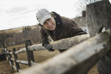 A man leaning against a post and rail fence on a farm in winter.