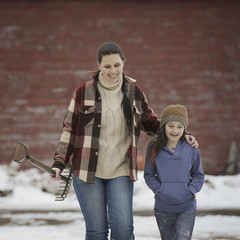 An organic farm in winter in New York State, USA. A woman and a young girl walking across a snowcovered farmyard.