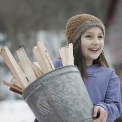 An organic farm in winter in New York State, USA. A girl carrying a bucket full of kindling and firewood.