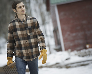 An organic farm in winter in New York State, USA. A man in a plaid shirt walking across snowcovered ground.