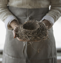 An organic farm in winter in New York State, USA. A woman in a work apron holding a woven twig bird nest.