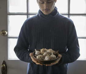 An organic farm in winter in New York State, USA. A young man holding a bow of garlic bulbs.