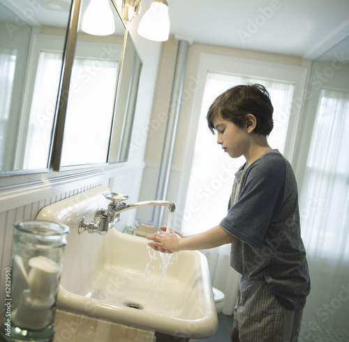 A boy standing in the bathroom, washing his hands under the tap.