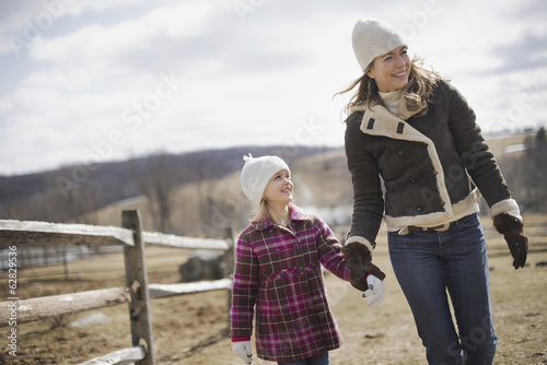 A woman and child walking along a path hand in hand on a farm in spring weather.