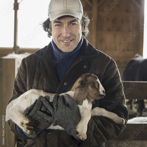 A man holding a small kid goat in his arms in a livestock pen.
