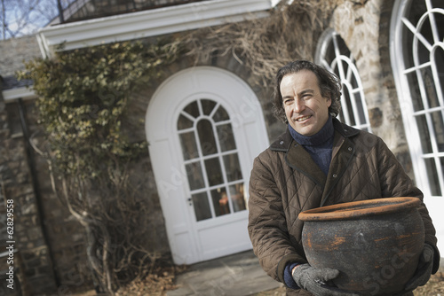Spring Planting. A man carrying a large terracotta pot across a courtyard.