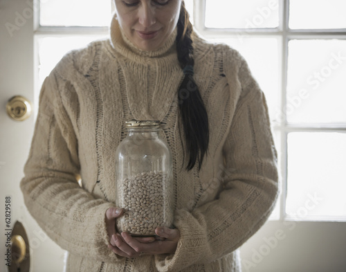 An organic farm in winter in New York State, USA. A woman in a cable knit sweater, holding a glass jar of white beans.