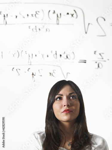 A young woman writing a mathematical equation with black marker on a clear seethrough surface and standing back to consider it.