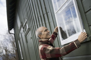 An organic farm in winter. Maintenance. A man holding a a storm window panel against the window frame.