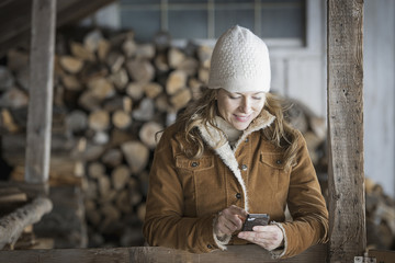 An organic farm in upstate New York, in winter. A woman in sheepskin coat and woollen hat using a cell phone.
