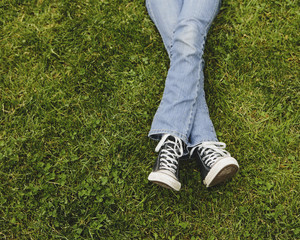 A ten year old girl lying on the grass. Cropped view of her lower legs. Wearing sneakers and faded blue jeans. Legs crossed at the ankles.