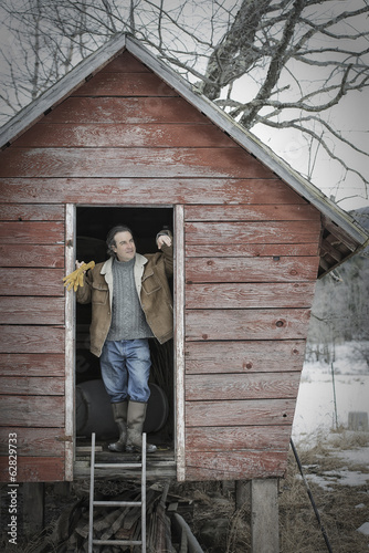 An organic farm in upstate New York, in winter. A man standing in the doorway of a henhouse.