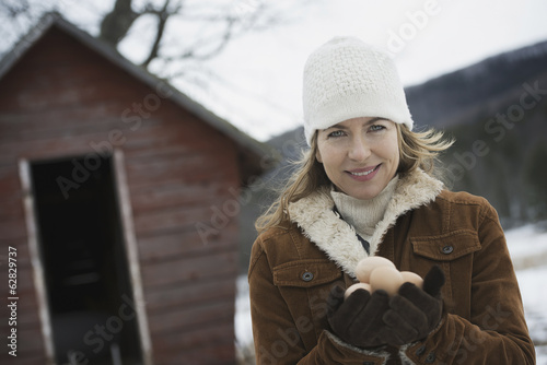 An organic farm in upstate New York, in winter. A woman holding a clutch of hen's eggs in her hands.