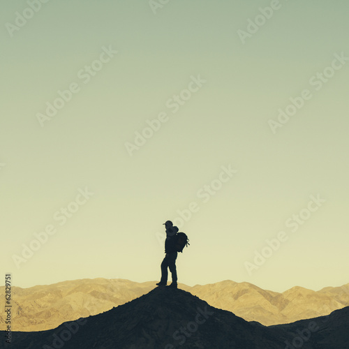 Silhouette of a male hiker wearing a backpack and standing on a hilltop in Death Valley national park.