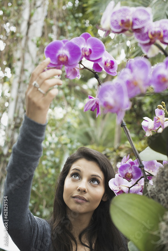 A young woman reaching up to admire an orchid growing in an indoor glasshouse in a botanical garden in New York City.
