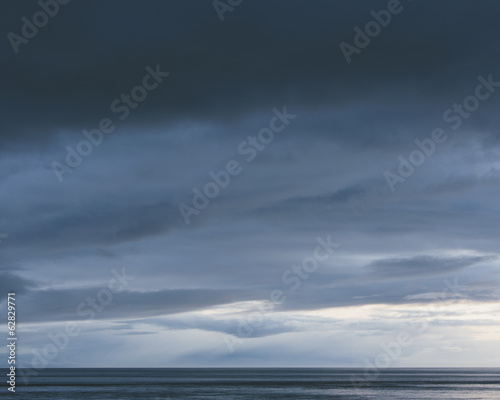 The sea and sky over Puget Sound in Washington, USA. The horizon with light and cloud layers above. Gathering storm clouds.