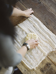 A domestic kitchen table. A view from above of a woman wrapping fresh pastry in a muslin cloth to keep it fresh.