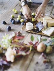 A woman at a domestic kitchen table. Arranging fresh fruit, black and green figs on a cheese board. Organic food. From farm to plate.