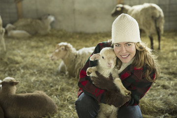 An Organic Farm in Winter in Cold Spring, New York State. A family working caring for the livestock. A woman holding a small lamb.