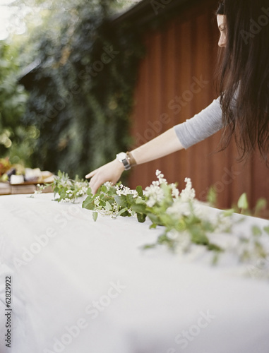 A woman with long hair leaning over a table laid outside with a white cloth and a central foliage table decoration. Place settings.