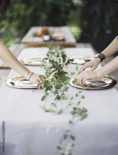 Two people leaning over a table laid outside with a white cloth and a central foliage table decoration. Placing cutlery and plates on a tabletop.