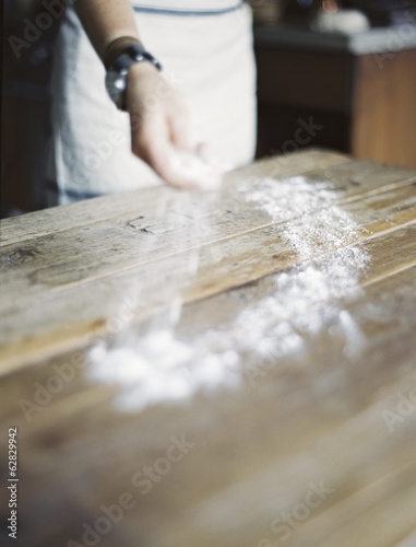 A domestic kitchen. A woman cooking. Spreading flour across a tabletop.