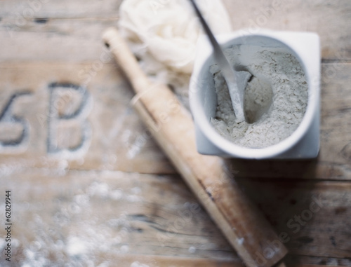 A domestic kitchen. A small group of objects. A rolling pin and jar of flour on a worn tabletop. View from above.