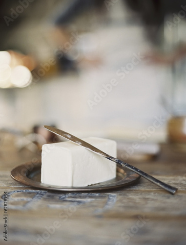 A domestic kitchen. A woman in the background. A slab of fresh organic butter, on a wooden dish.