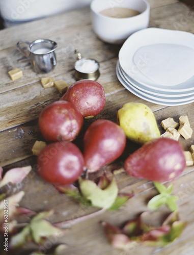A domestic kitchen tabletop. A small group of fresh organic pears and a stack of white plates.
